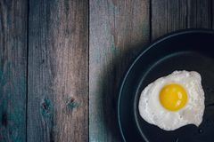 Top view fried eggs in a frying pan on a wooden table. Fried eggs in a frying pan on a wooden table, top view royalty free stock photo