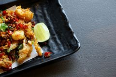 Top view of fried squid with chili and lemon in black plate stock photos