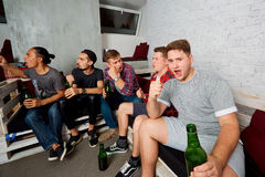 Friends together watching TV, drinking beer, yelling, laughing, having fun. Young fans in the room rooting for their team in foot. Top view friends with a bottle royalty free stock image
