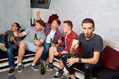 Friends together watching TV, drinking beer, yelling, laughing, having fun. Young fans in the room rooting for their team in foot. Top view friends with a bottle stock image