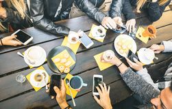 Top view of friends drinking cappuccino at coffee shop restaurant. People having fun together eating cakes and using mobile smart phones at cafe bar stock images