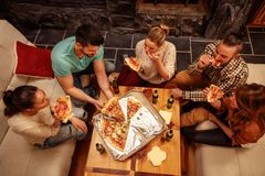 Top view of friends eating pizza and having party. At home Royalty Free Stock Images