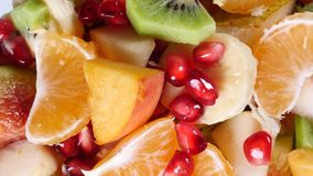 Top view of a fruit salad with mandarin, oranges, kiwi, pomegranate seeds, figs, banana and peaches stock footage