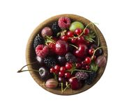 Top view. Fruits and berries in bowl on white background. Ripe currants, raspberries, cherries, strawberries, gooseberries, blackb. Erries, mulberries Royalty Free Stock Image