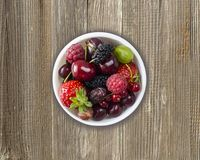 Top view. Fruits and berries in bowl on wooden background. Ripe currants, raspberries, cherries, strawberries, gooseberries, black. Berries, mulberries royalty free stock images
