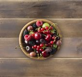 Top view. Fruits and berries in bowl on wooden background. Ripe currants, raspberries, cherries, strawberries, gooseberries, black. Berries, mulberries Royalty Free Stock Photos