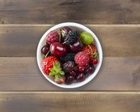 Top view. Fruits and berries in bowl on wooden background. Ripe currants, raspberries, cherries, strawberries, gooseberries, black. Berries, mulberries stock images