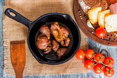 Top view roasted chicken giblets in pan and bread. Top view frying pan with delicious roasted chicken giblets with rye bread, tomatoes and wooden spatula Royalty Free Stock Photography