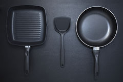 Top view frying pan and plastic spade on black table background. Stock Images