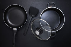 Top view frying pan and pot on black table. Stock Image