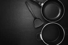 Top view frying pan and pot on black table. Stock Photography