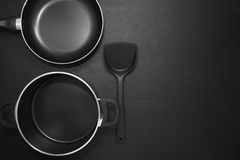 Top view frying pan and pot on black table. Royalty Free Stock Image