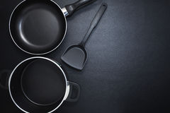 Top view frying pan and pot on black table. Royalty Free Stock Images
