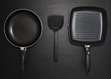 Top view frying pans and plastic spade on black table background Stock Photo