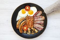 Top view, full English Breakfast in cooking pan with sausages, fried eggs, beans and bacon on a white wooden background. From above Royalty Free Stock Image