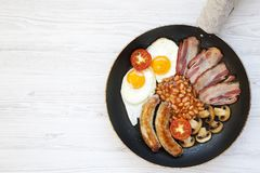 Top view, full English Breakfast in cooking pan with sausages, fried eggs, beans and bacon on a white wooden background. Copy spac. E. Flat lay. From above Stock Image