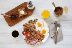 Top view, full English breakfast with fried sausages, eggs, beans, bacon and toasts. White wooden background. From above, overhead. Flat lay Royalty Free Stock Photos