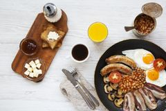 Top view, full English breakfast in a pan with fried eggs, beans, sausages, bacon and toasts on white wooden background. Overhead shot, flat lay Royalty Free Stock Photo