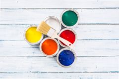 Top of view full of multicolored paint cans with brush on table.  stock photos