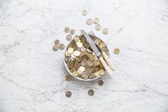 Top of view full plate of euro coins on marble table. Money food concept cash banknote fork knife currency finance background euros economy bill white wealth stock photo