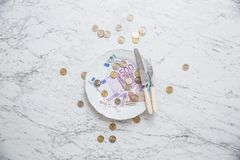 Top of view full plate of euro money coins and banknotes. Food concept cash fork knife currency finance background euros economy bill white wealth rich royalty free stock photography
