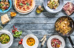 Top of view full table of italian meals on plates and pan. Pizza pasta risotto soup and fish vegetable salad royalty free stock photography