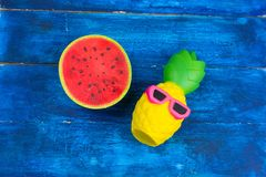 ce3e3d8ce0d8 Funny pineapple toy in sunglasses and squishy toy watermelon on a blue wooden  background. Top