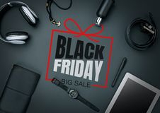 Top view of gadgets with black friday lettering on black background