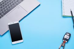 Top view upon gadgets on blue background, the composition of a laptop, white headphones, phone, glass with a drink and car keys royalty free stock image