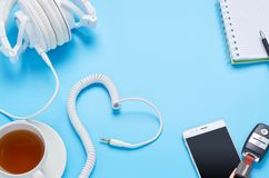 Top view upon gadgets on blue background, composition of white headphones, phone, tablet, glass with a drink and car keys stock image