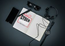 Top view of gadgets with cyber monday lettering on black background