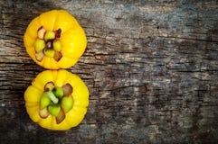 Top view.  Garcinia cambogia fresh fruit on wood background.  Fr. Top view. Two garcinia cambogia fruit on wood background and free form copy space. Garcinia Stock Photography