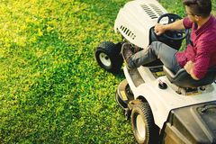 Top view of gardner using lawn mower for cutting grass, portrait of healthy lifestyle and weekends. Top view of man using lawn mower for cutting grass, portrait Stock Photography