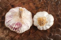 Top view on garlic bulbs, cloves covered in purple skin with cra. Ck, in old wooden bowl Stock Images