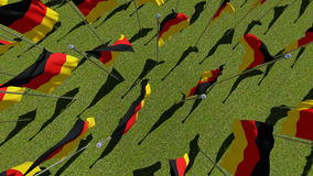 Top view on German flags blowing in the wind in green field. Royalty Free Stock Photo