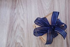 top view of gift box present with blue ribbon space on wooden background Stock Image