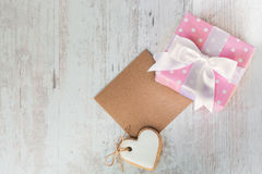 Top view of a gift box wrapped in pink dotted paper, heart shaped love cookie and an empty kraft card over a white wood background Stock Images