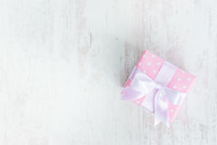 Top view of a gift box wrapped in pink dotted paper and tied satin bow over a white wood background. Royalty Free Stock Images