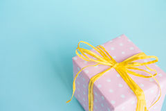 Top view of a gift box wrapped in pink dotted paper and tied yellow bow over light blue background. Royalty Free Stock Photo