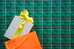 Top view on gift box with yellow bow ribbon and orange shopping bag on bright green orange Scotch cage ornament background. Copy royalty free stock photography
