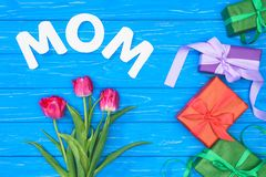 Top view of gift boxes, pink tulips and word mom on blue table, mothers day concept stock photos