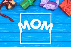Top view of gift boxes and word mom in frame on blue table, mothers day concept stock image