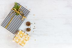Top view of gift boxes wrapped in black and white striped and golden dotted paper with pine and cones on a white wood background. Royalty Free Stock Photography