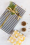 Top view of gift boxes wrapped in black and white striped and golden dotted paper with pine and cones on a white wood background. Stock Photos