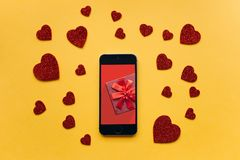 Top view. A gift on the phone screen. Nearby are symbols in the form of a heart on a yellow background. Celebrating the event Royalty Free Stock Photography
