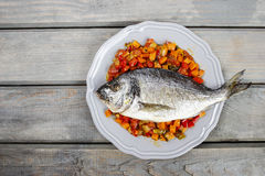 Top view of gilt-head bream fish. On wooden background. Symbol of healthy living Stock Photos