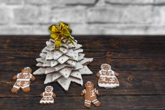 Top view of gingerbread Christmas tree with cute gingerbread fam. Ily on wooden desk near snow-covered brick wall. Mockup for seasonal offers and holiday post Royalty Free Stock Photography