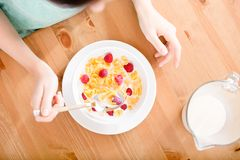 Top view of girl eating cereals with strawberry and milk Royalty Free Stock Photography