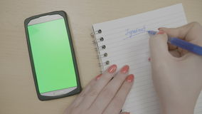 Girl planning to cook dinner writing down recipe ingredients on her agenda while looking at smartphone with green screen -. Top view of girl hands planning to stock video footage