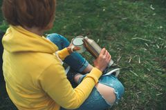 Top view girl holding in hands cup of hot tea on green grass in outdoors nature park, beautiful woman hipster enjoy drinking cup royalty free stock photography